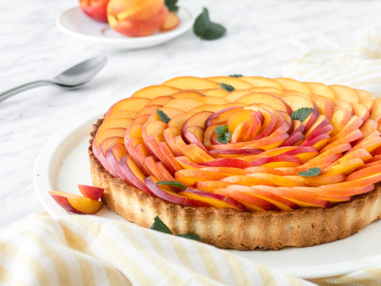 side view of a vegan nectarine tart with neactarines in the background