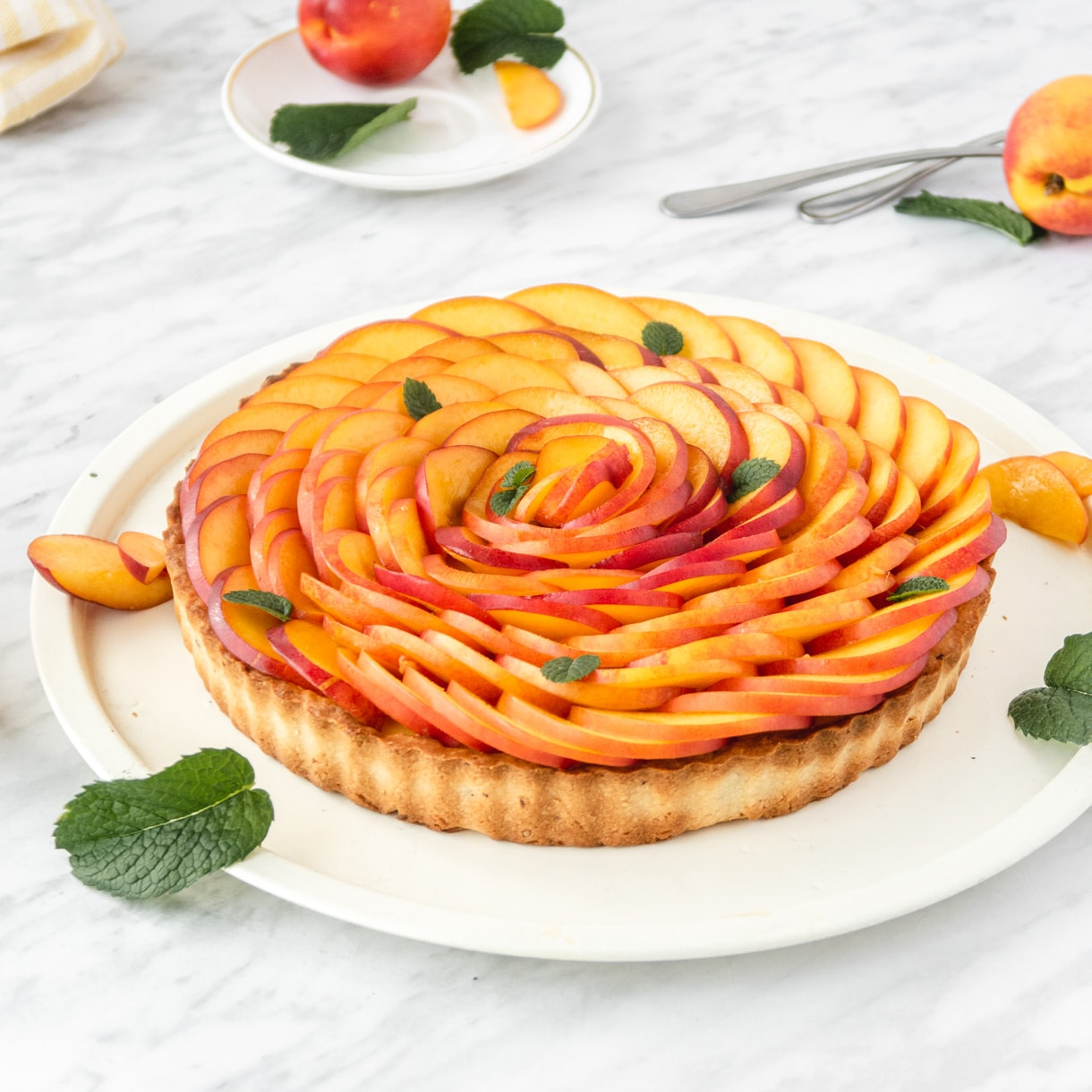 3/4 view of a nectarine tart on a white plate with mind leaves garnishes