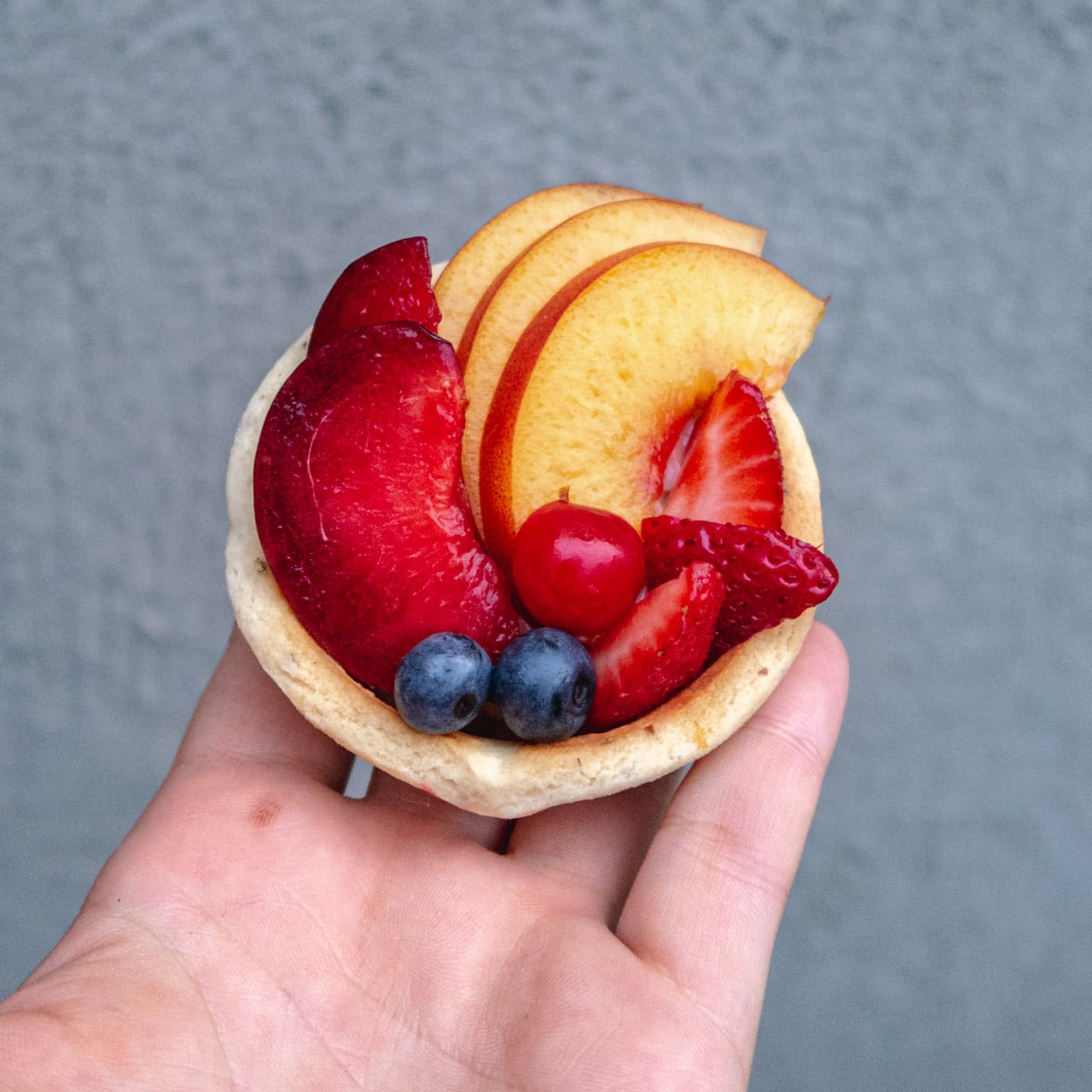 vegan fresh fruit tartlets held up in the palm of a hand