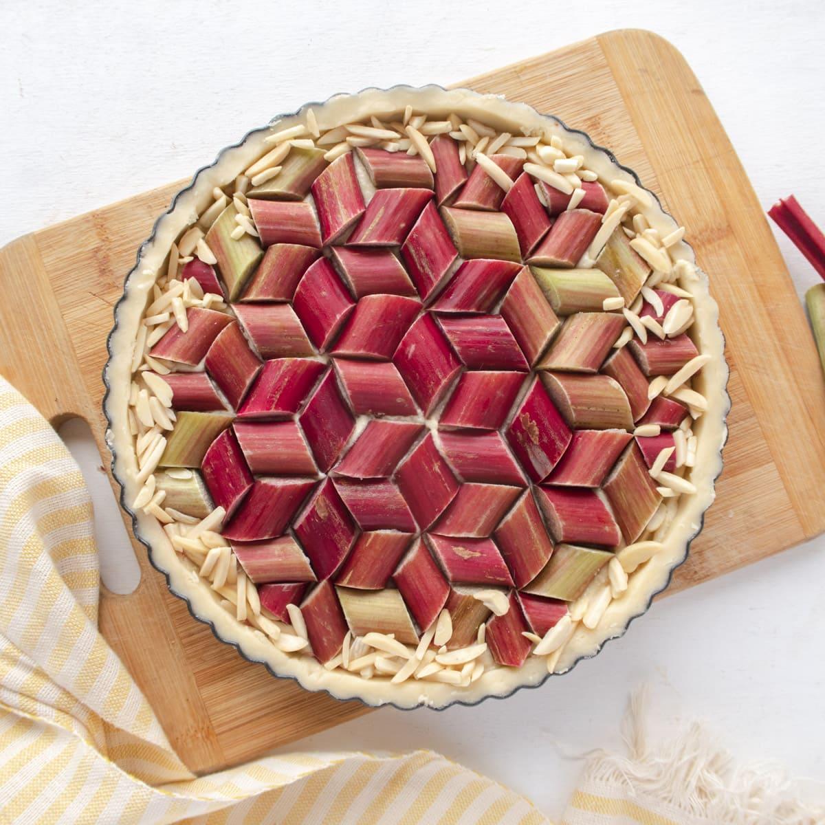 Top down view of a uncooked tart on a cutting board with a geometric rhubarb pattern on top of the tart