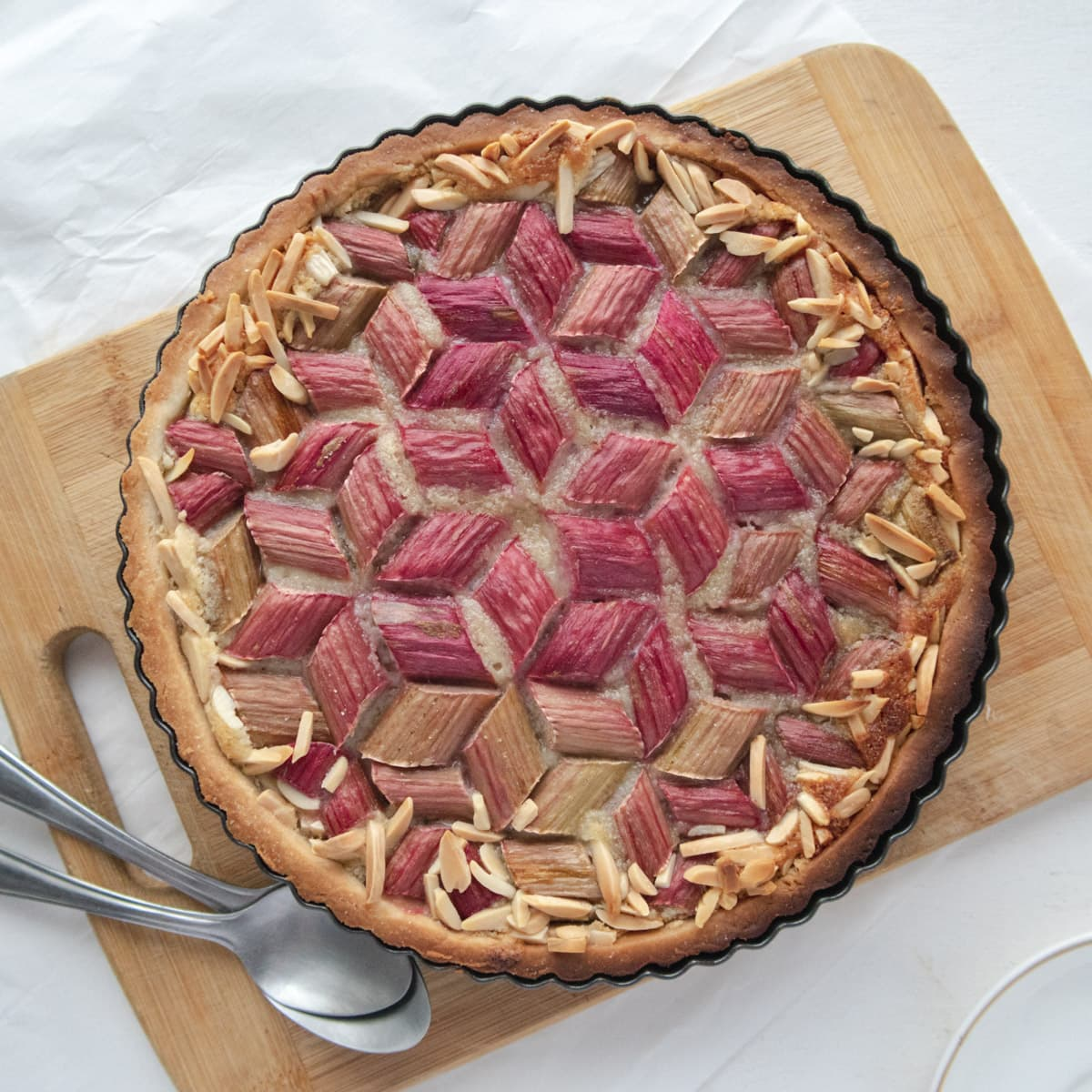 geometric rhubarb tart placed on a cutting board with some spoons
