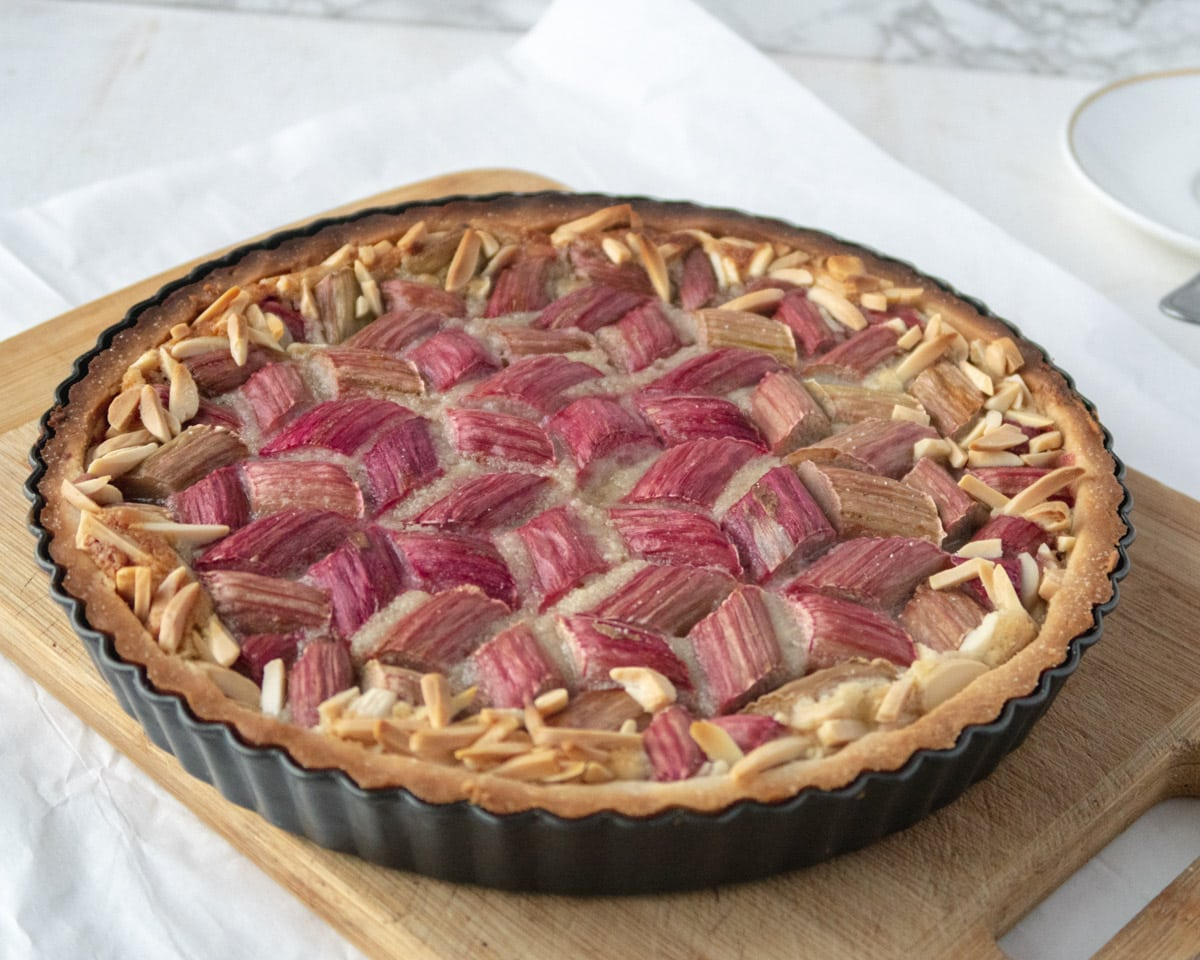 side view of a cooked rhubarb and frangipane tart on a cutting board