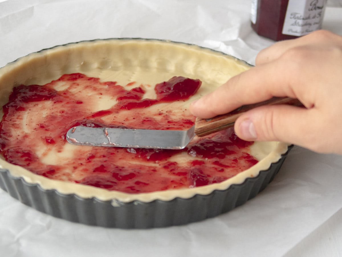 raw tart shell with strawberry jam being spread on the bottom