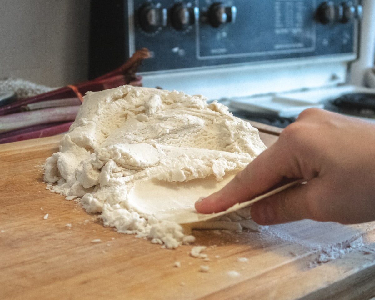 vegan pastry dough being squished with a bench scraper onto a wooden cutting board ( fraiser technique)