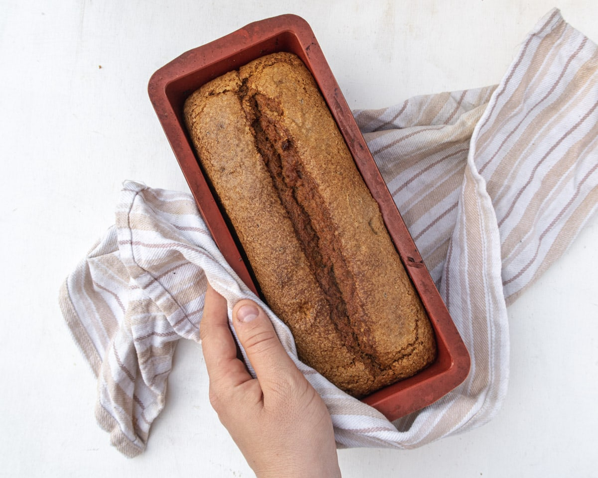 Vegan Bourbon pumpkin bread in the pan, wrapped in a dish towel