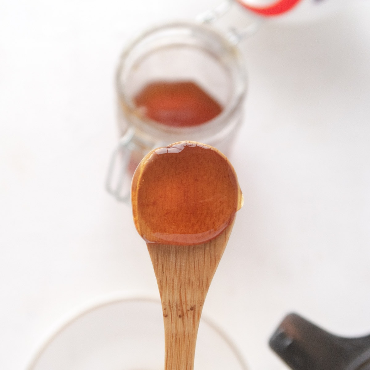 vegan honey on a bamboo spoon with the jar blurry in the backgorund