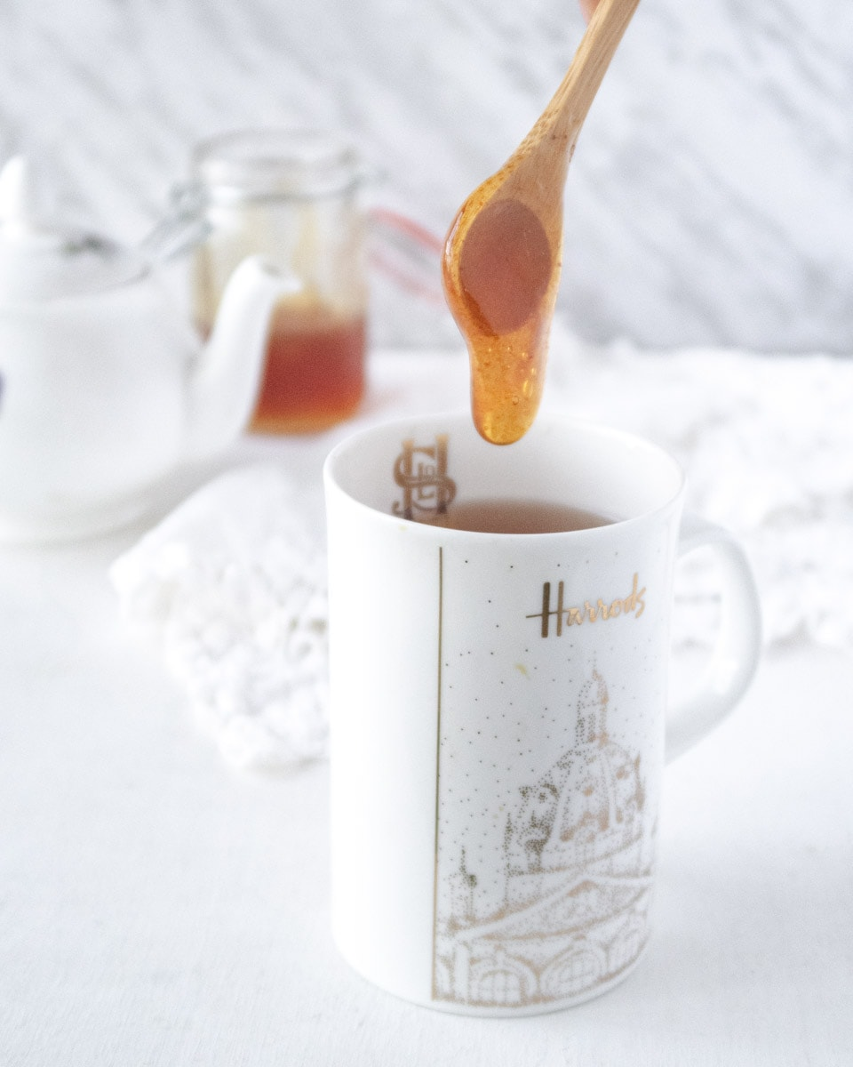 a spoonfull of vegan honey being dropped in a cup of tea