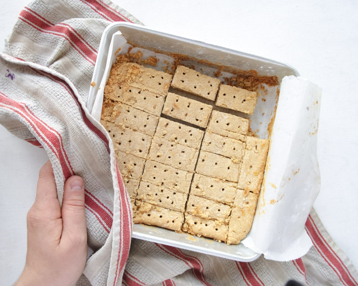 vegan shorbread cookies in a square pan on top of a red stripped dishcloth