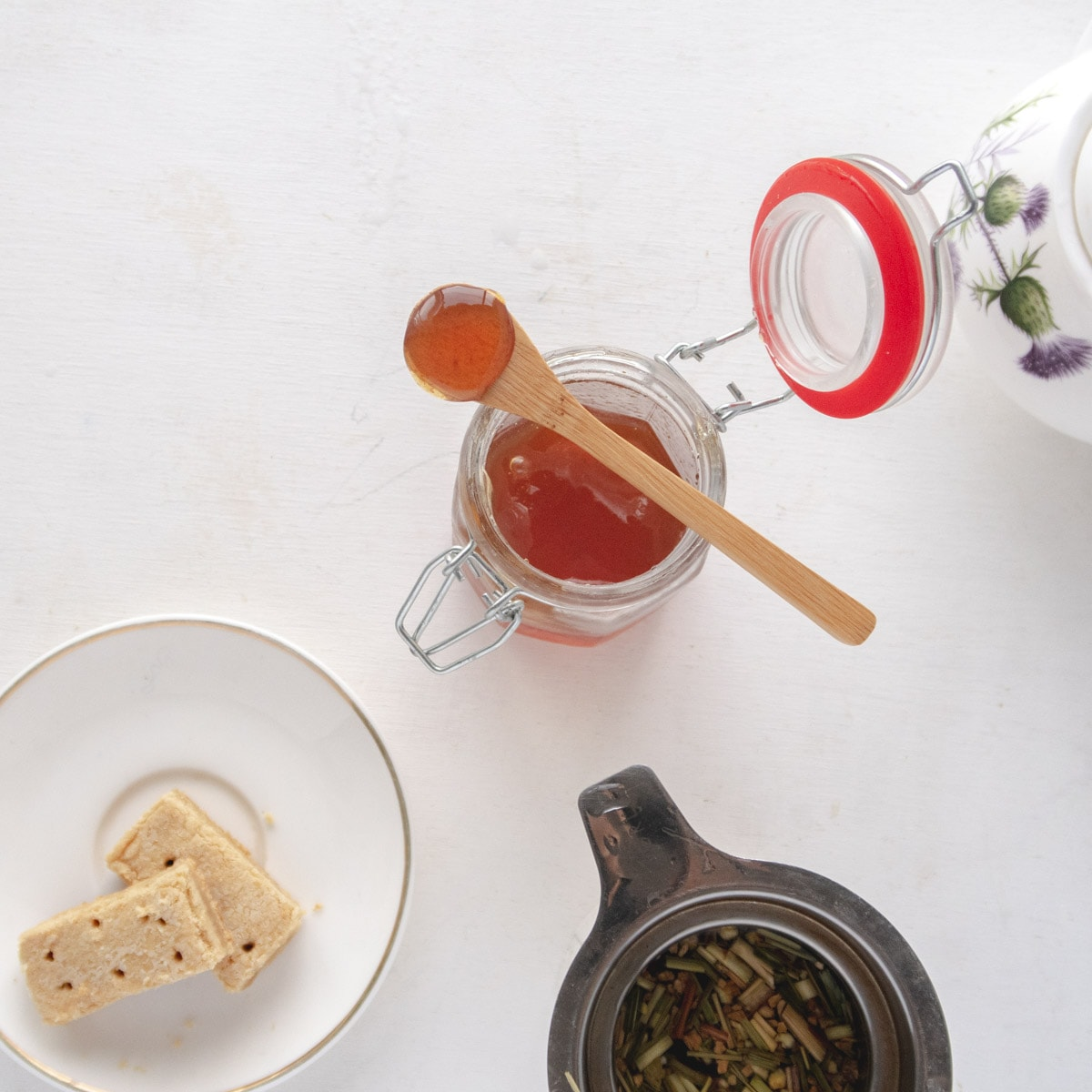 flatlay of a jar of honey, some shortbreads and some tea