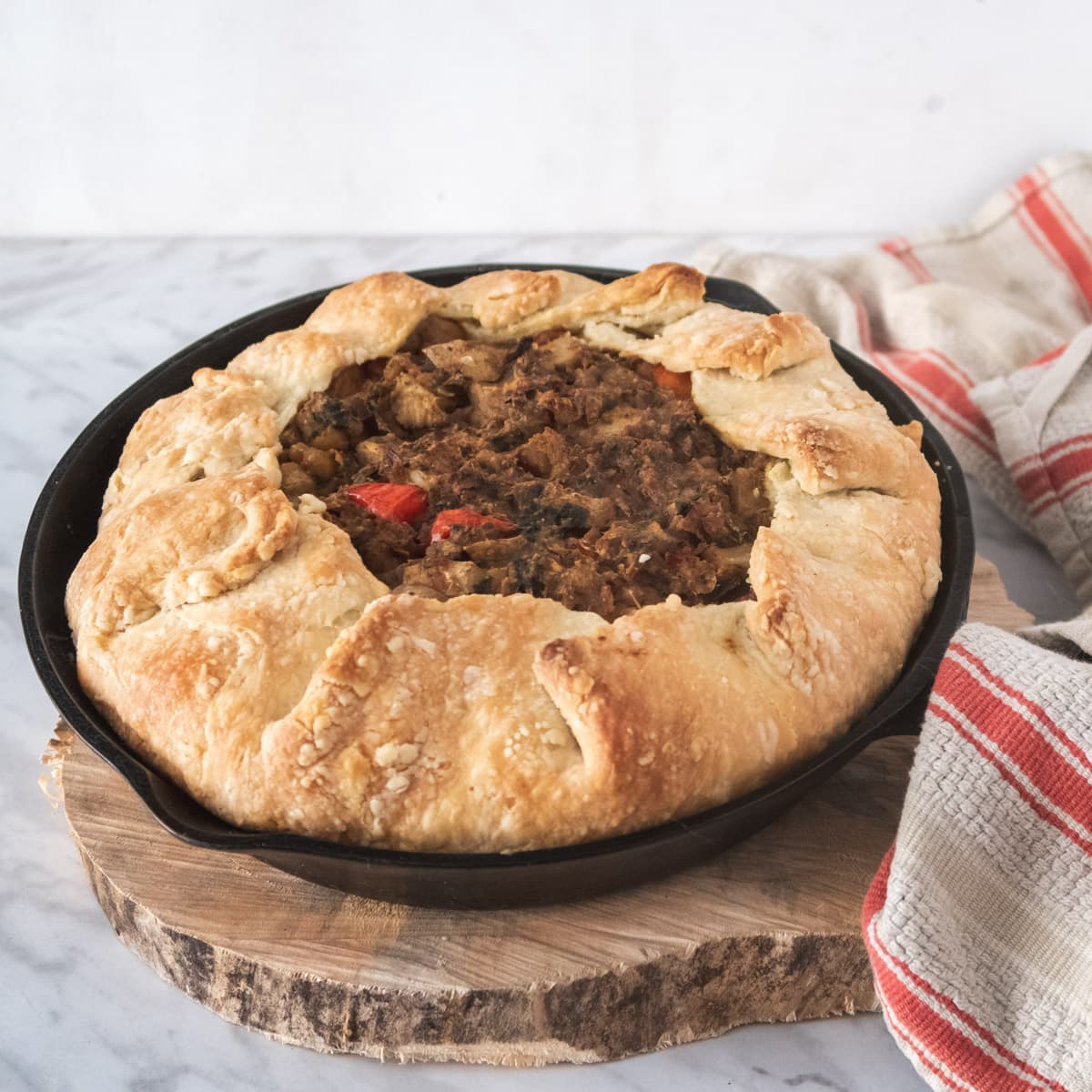 curried chickpea pie in a cast-iron skillet on top of a slice of wood
