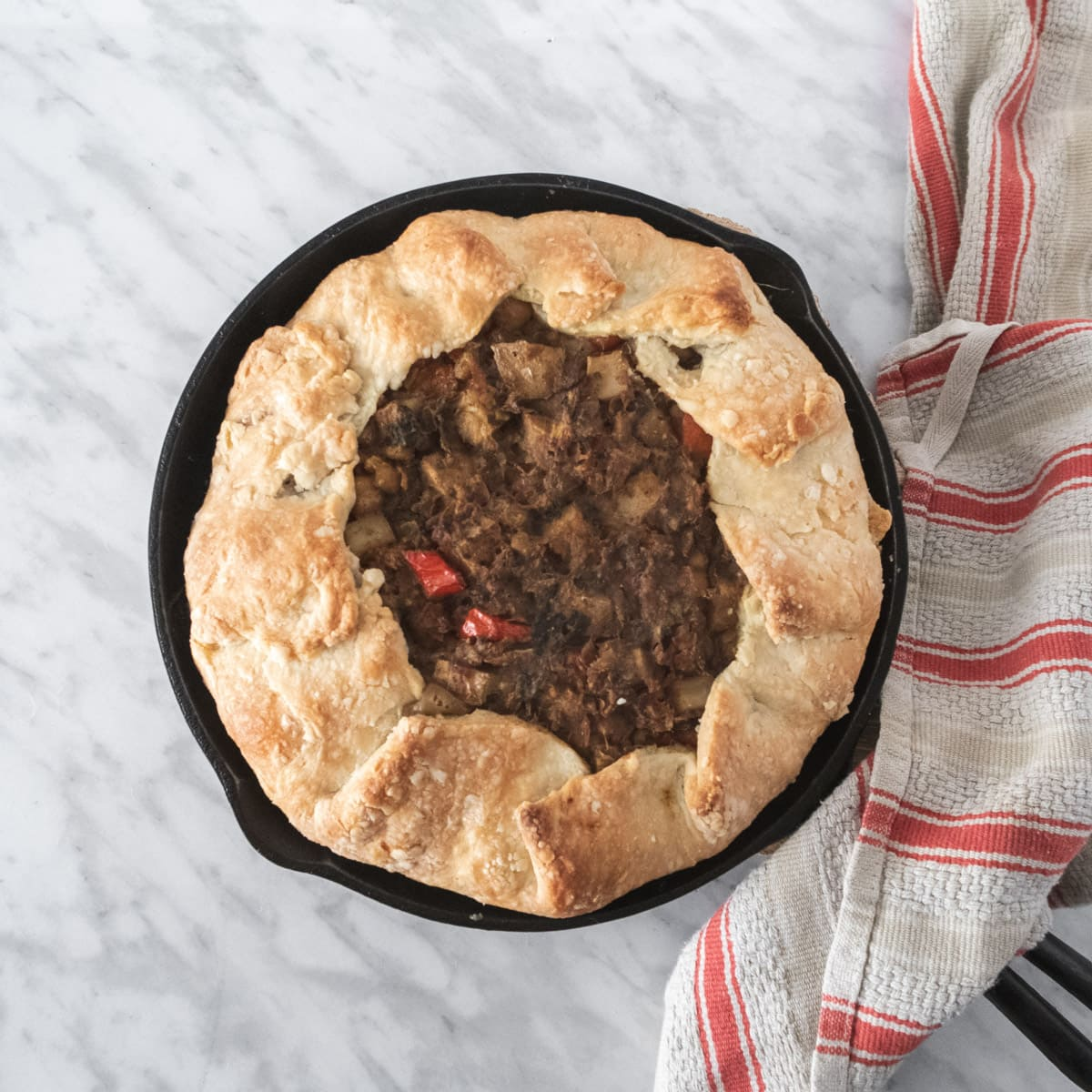top down view of a rustic chickpea pie on a white background with a red-stripped dishtowel