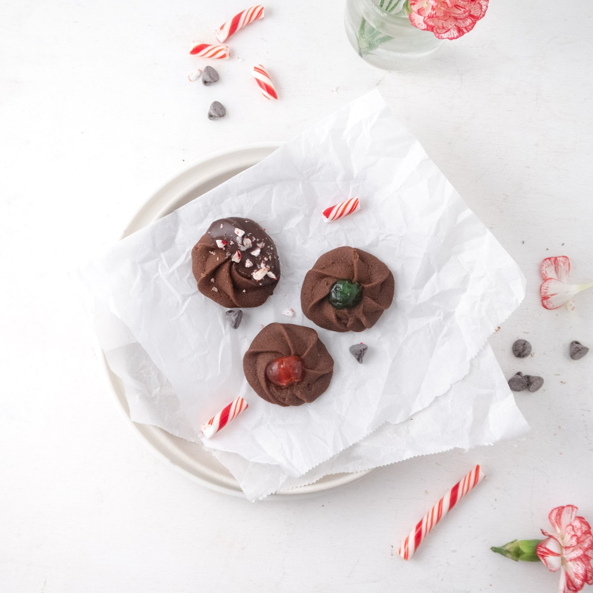 top view of 3 differently decorated chocolate butter cookies on a plate with some candy canes and flowers on the table