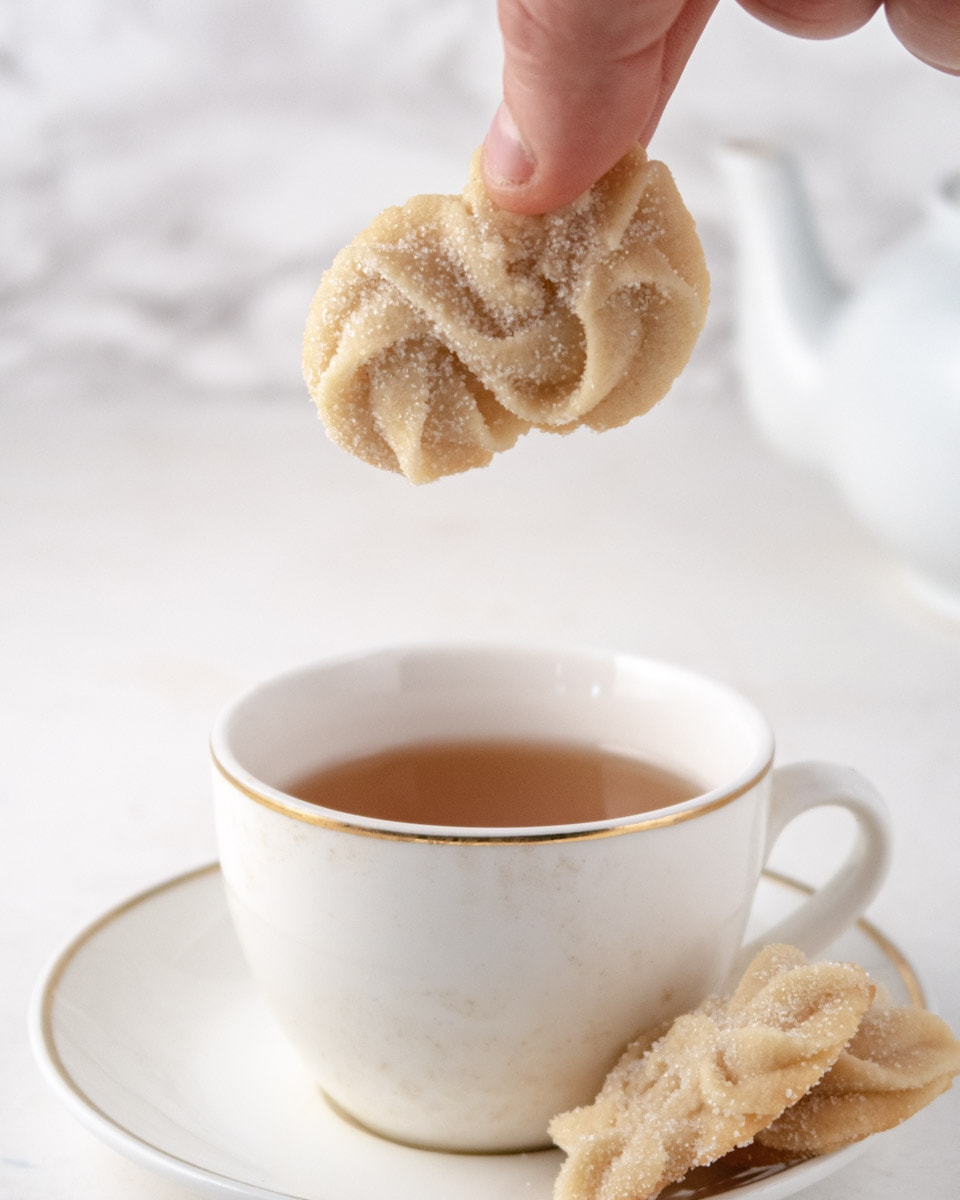 Vegan Danish butter cookie held by 2 fingers on top of a cup of tea