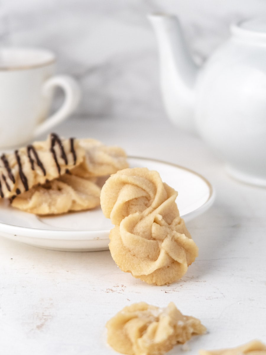 Danish butter cookies resting on a small plate with a teapot in the background