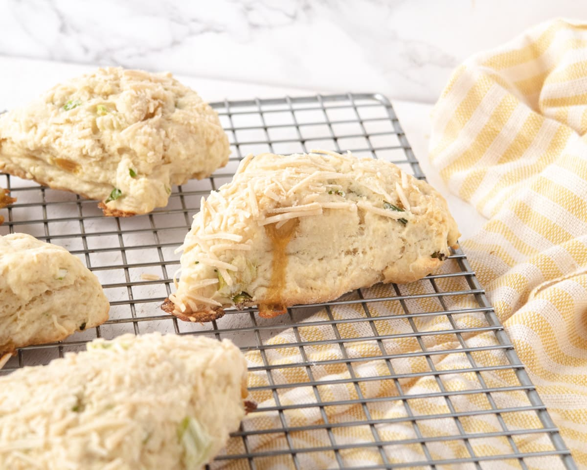 vegan herb and cheddar savoury scones on a wire cooling rack with a yellow-stripped dishtowel