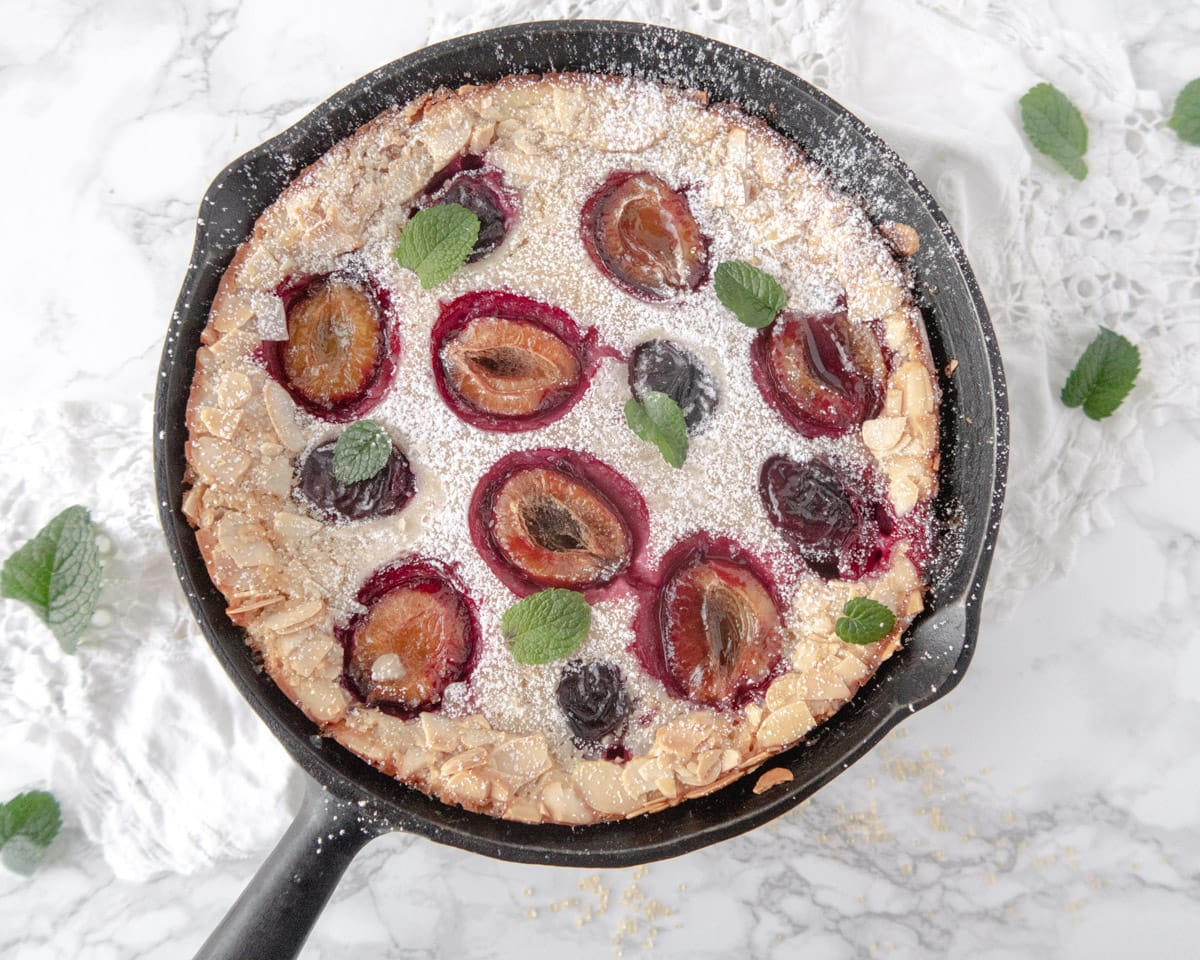 Top down view of a plum clafoutis in a cast iron skillet
