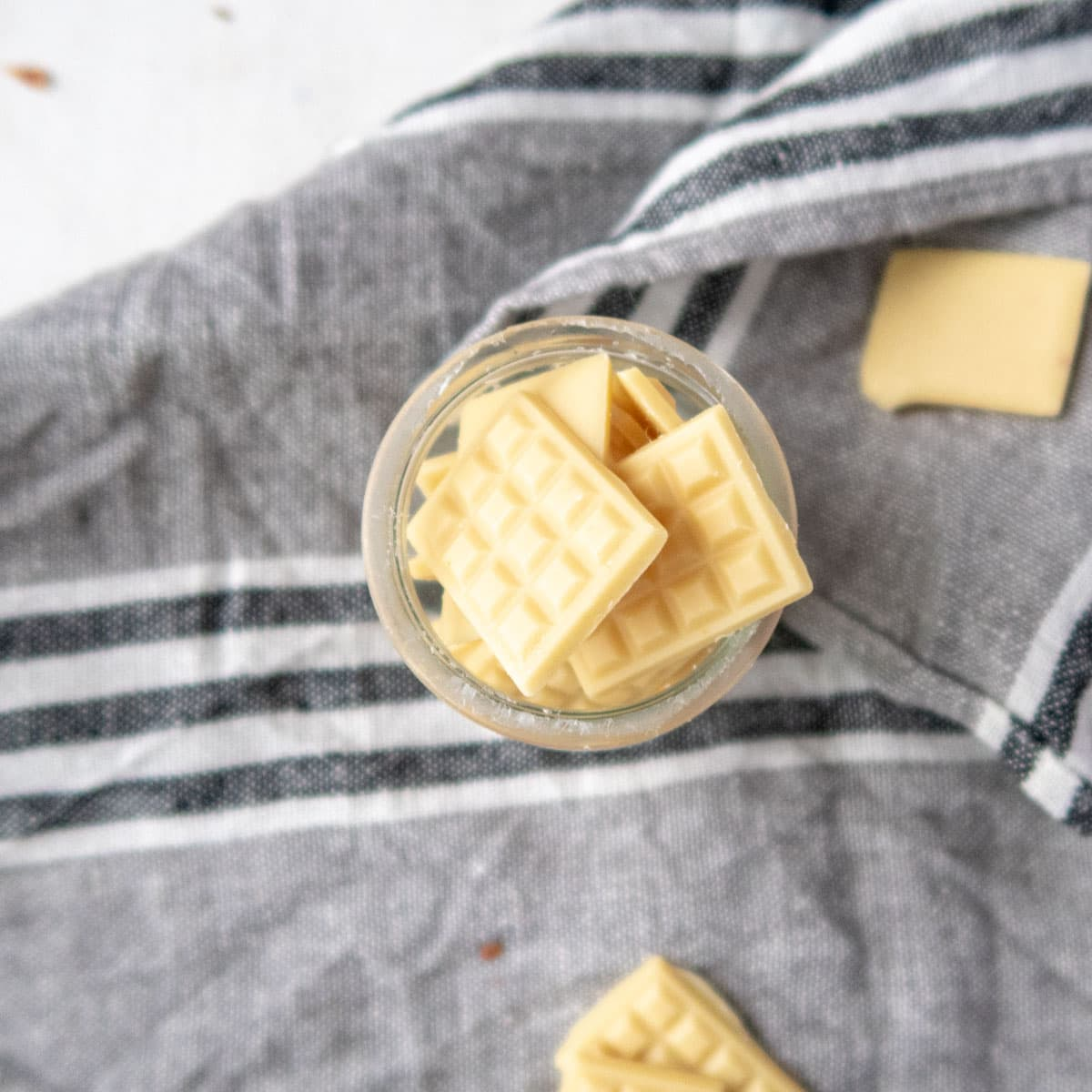 mini vegan white chocolate bars in a jar on top of a grey towel