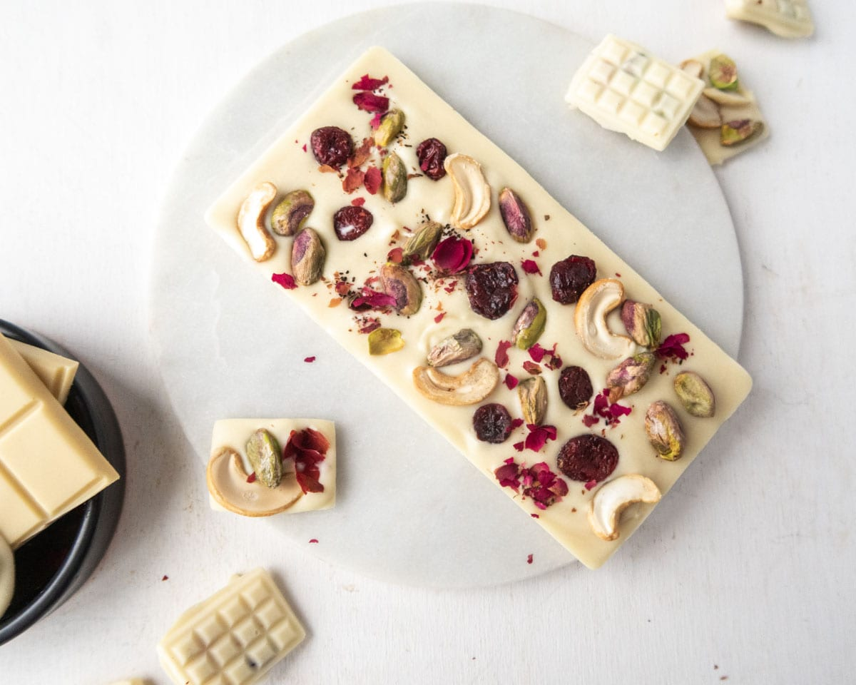 a large vegan white chocolate bar garnished with pistachioes, cashewes,dried cranberries and rose petals