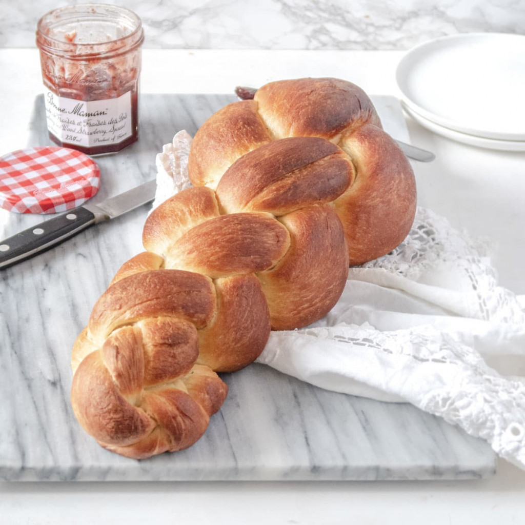 vegan butterzopf (Swiss braided bread) on a marble slab with some jam in the background