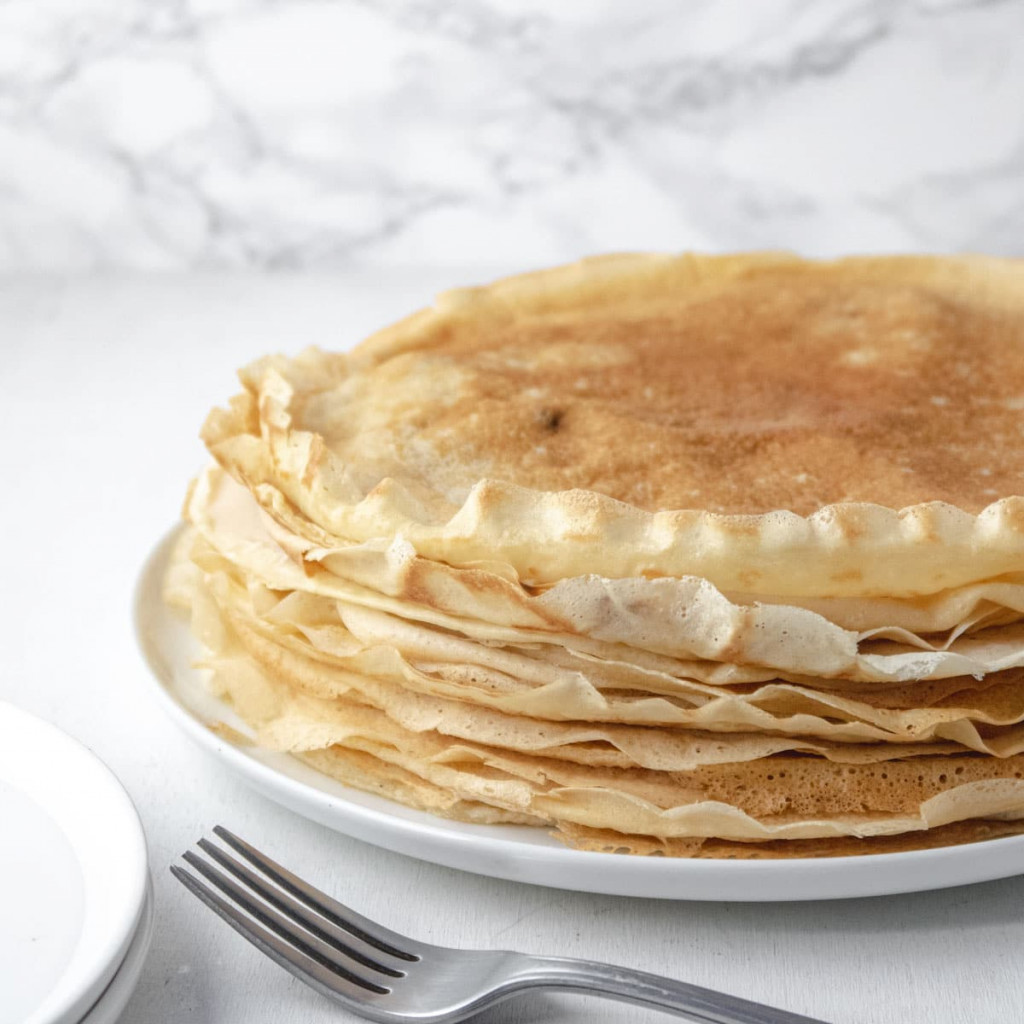 a tall stack of vegan crèpes on a plate with maple syrup in the background
