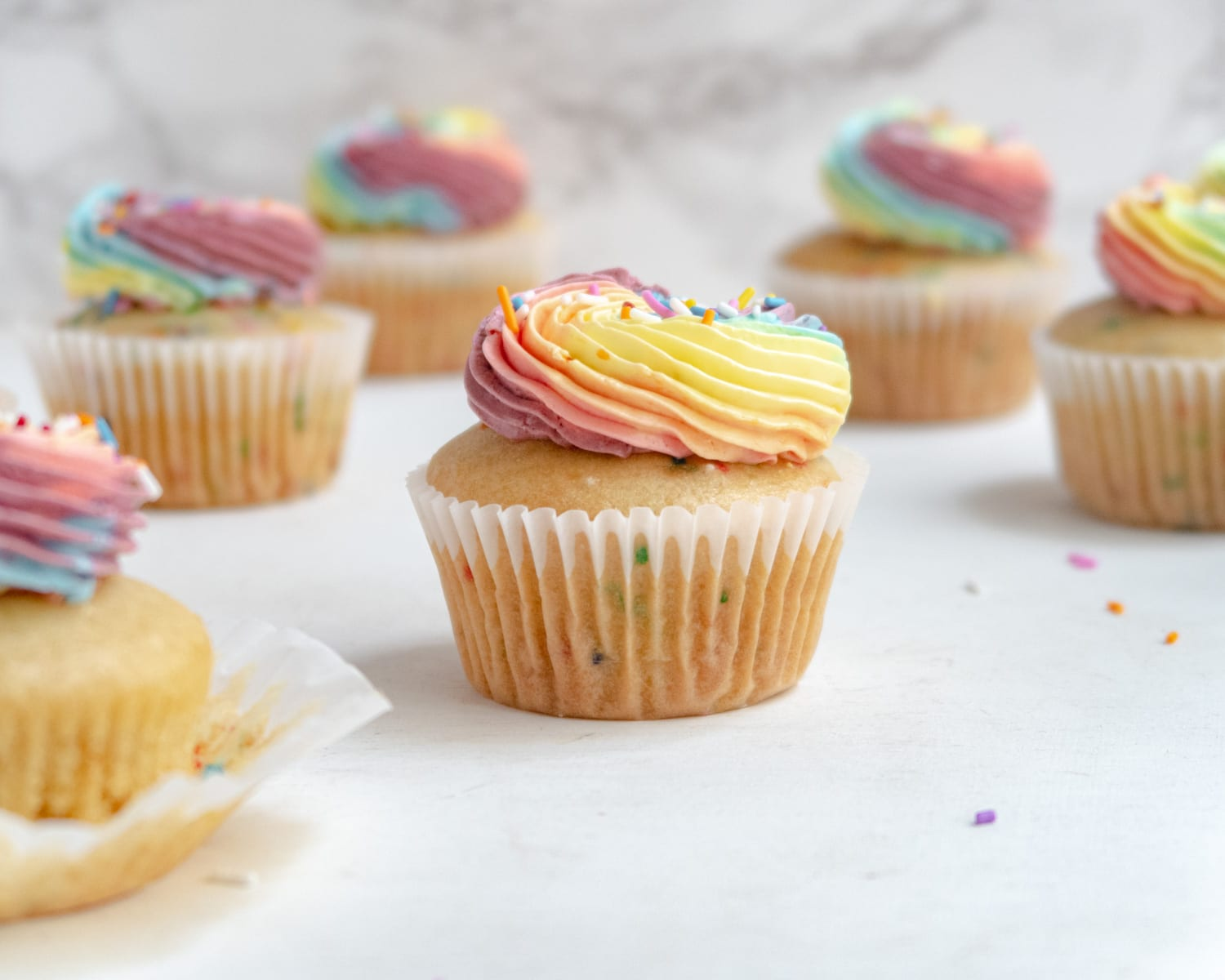 Pride cupcake with blury funfetti cupcakes in the background