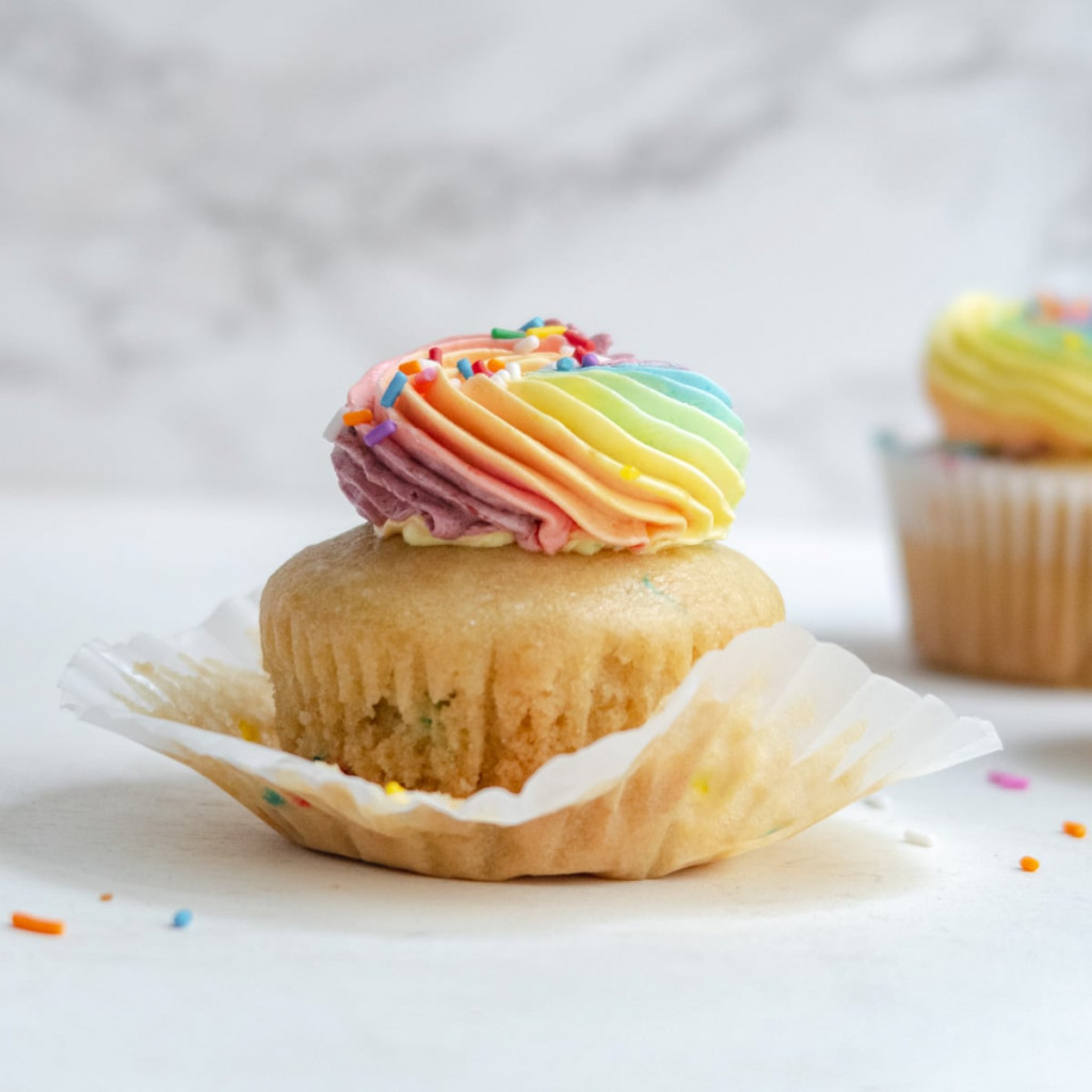 partially unwrapped vegan funfetti cupcake with pastel rainbow icing