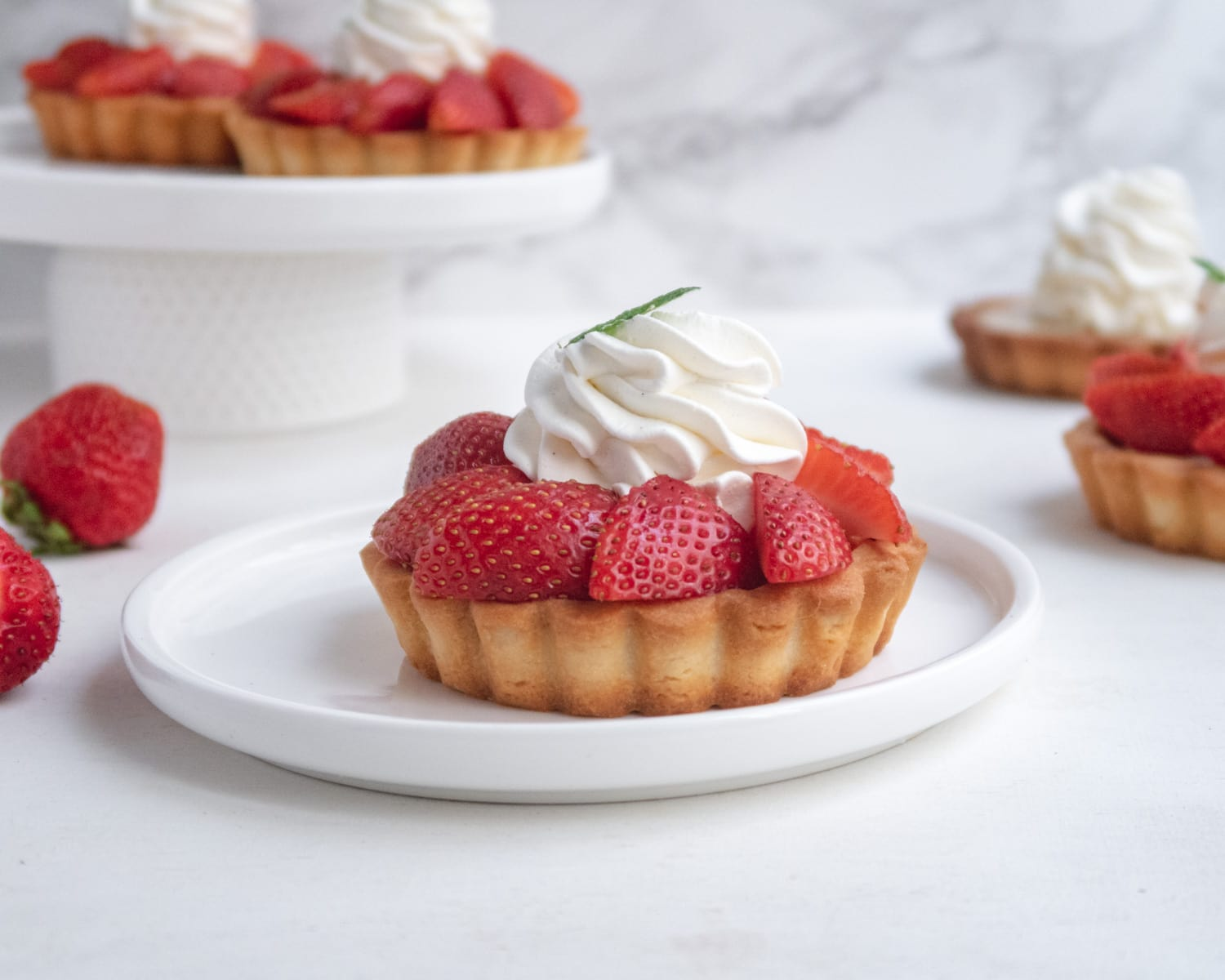 side view of a vegan fresh strawberry and rhubarb tartlets on a plate with more tartlets in the background