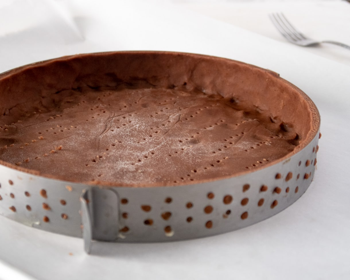 unbaked chocolate shortcrust dough in a tart ring
