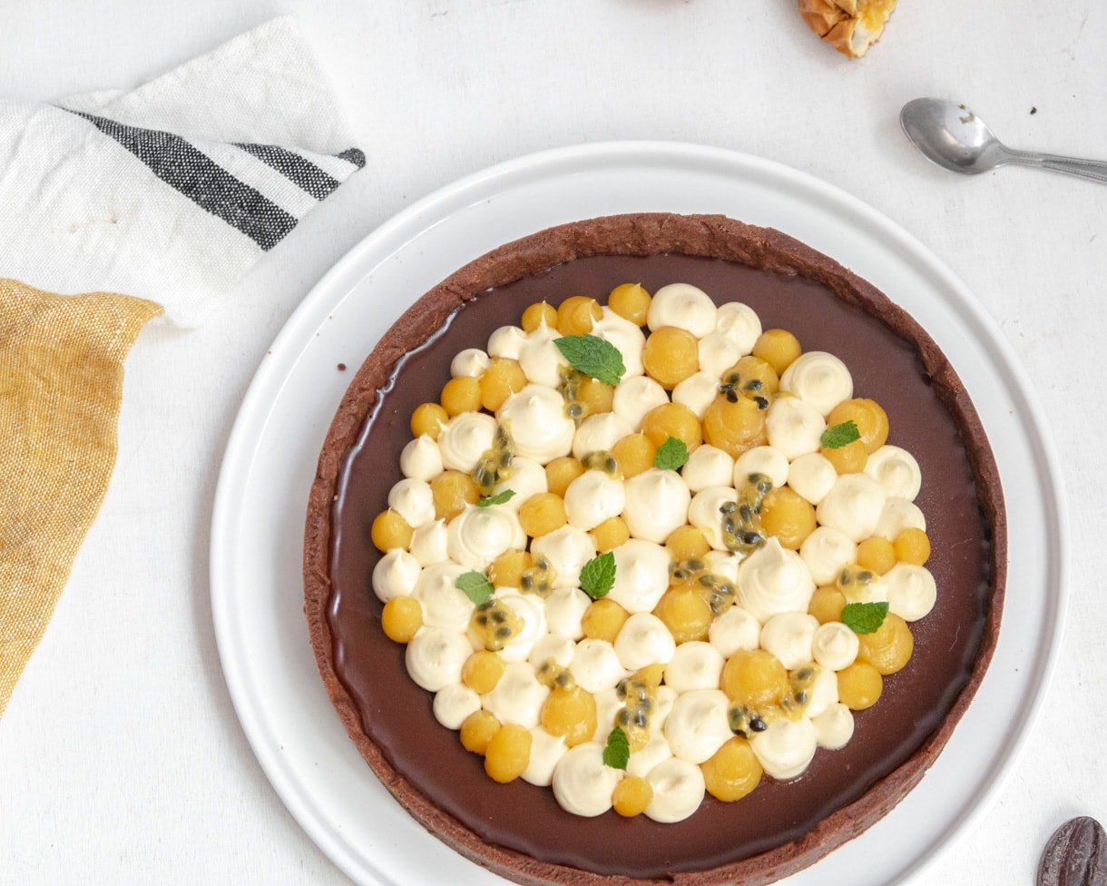top down view of the vegan passionfruit and chocolate tart on a white plate next to a mustard and gray stripped dishtowel