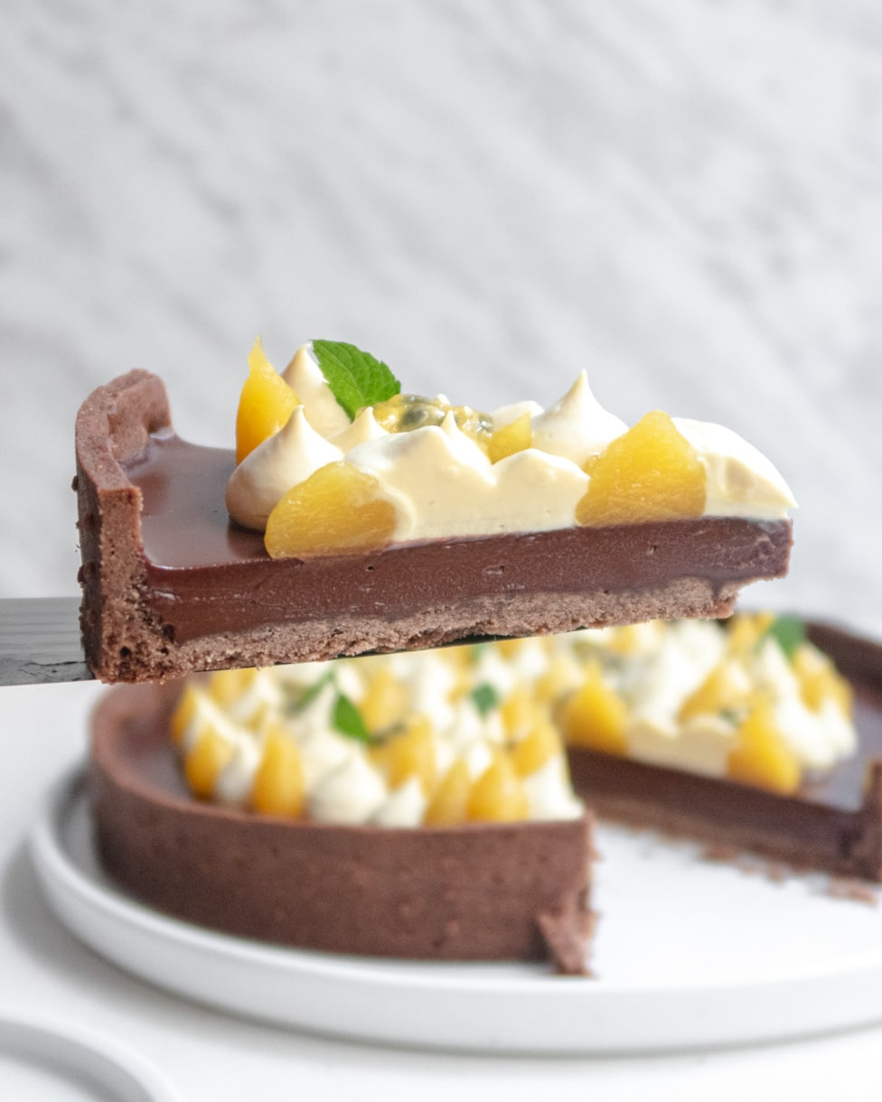 A slice of passionfruit chocolate tart held up in midair by a knife with the rest of the tart in the background