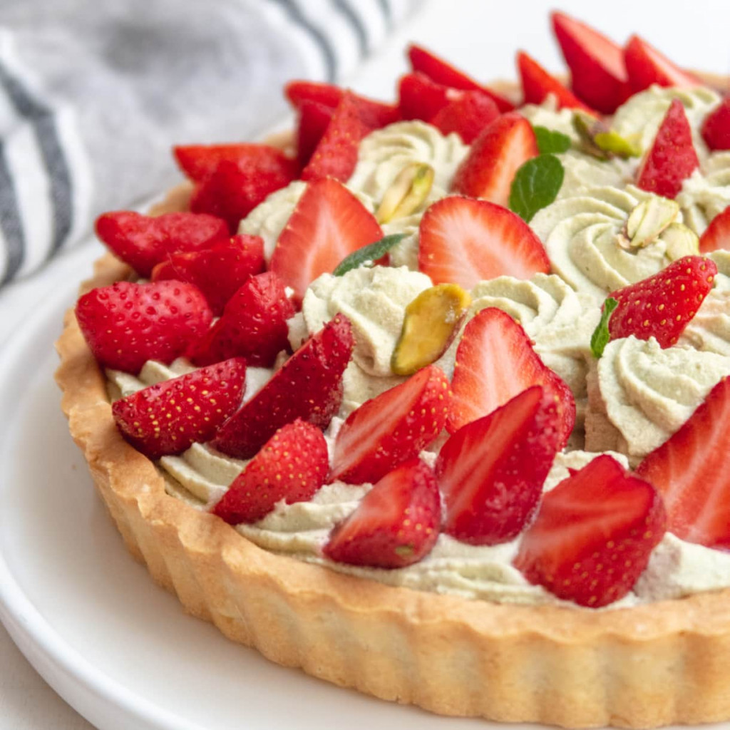 side view of a partial pistachio and strawberry tart on a white plate